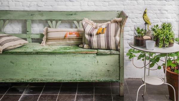 Vieux canapé vert avec des coussins contre un vieux mur de briques blanches