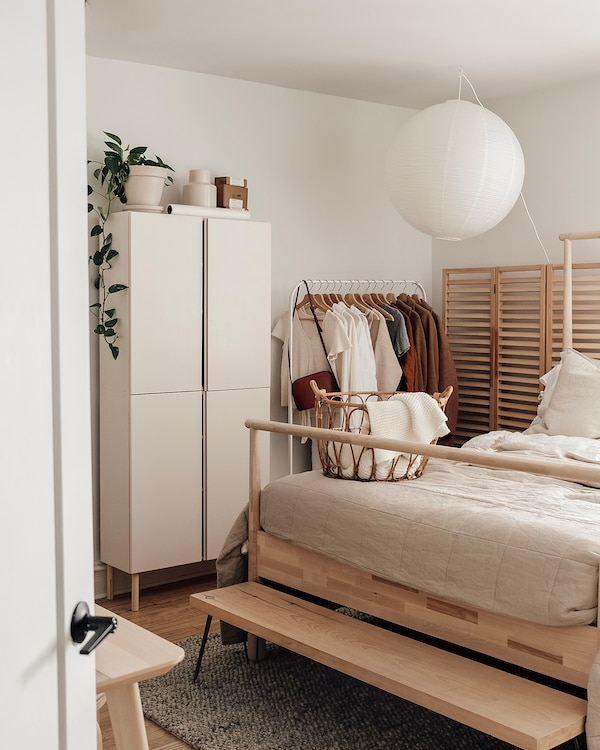 View of Emilie's airy bedroom with bed and clothing storage.