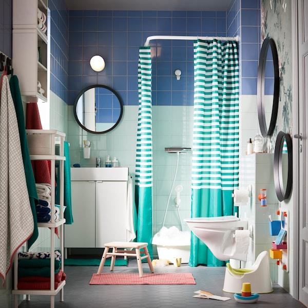 Vihreä ja sininen kylpyhuone, jossa on värikäs ja valkoinen sisustus ja paljon siirreltävää säilytystilaa aikuisille ja pienille lapsille.