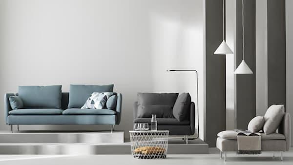 Vihreä SÖDERHAMN-sohva jolla on vaalea koristetyyny. Sohvan vieressä kaksi SÖDERHAMN-nojatuolia, musta ja harmaa.