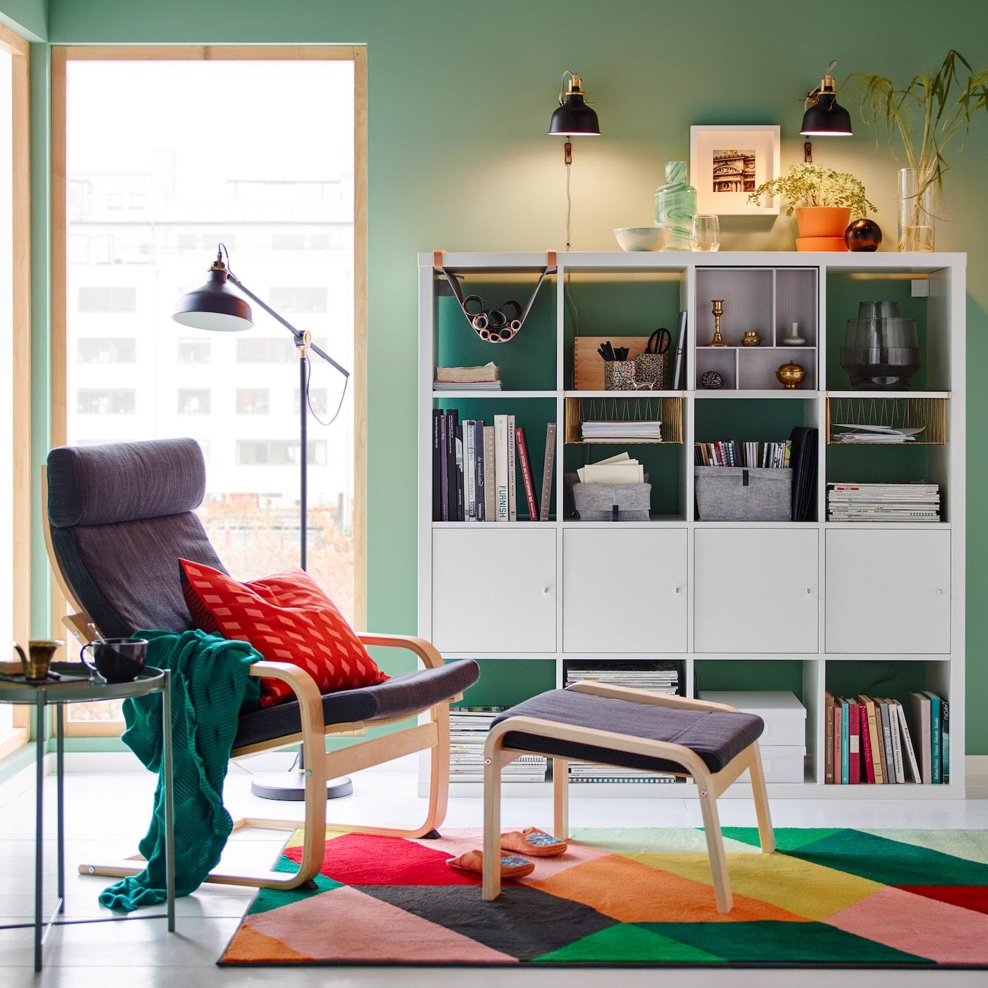Vihreän ja harmaan sävyin sisustettu lukunurkkaus, jossa monivärinen matto ja valkoiset hyllyt.