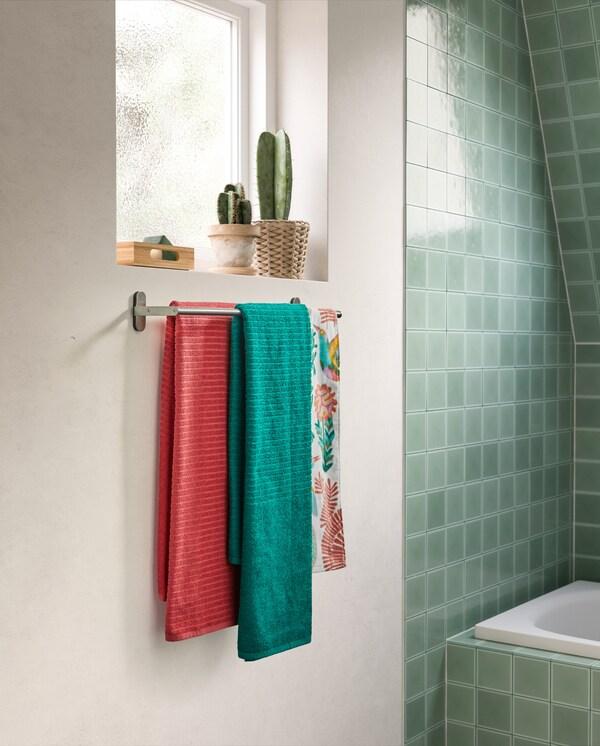 Vihreät ja pinkit pyyhkeet roikkuvat ruostumattomasta teräksestä tehdyssä BROGRUND-pyyhetangossa joka on kiinnitetty seinään ikkunan alle.
