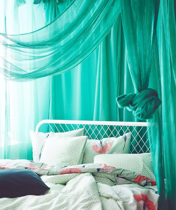 Vihreät laskostetut IKEA GRÅTISTEL verhot luovat huoneeseen yksityisyyttä mutta päästävät läpi vähän valoa.