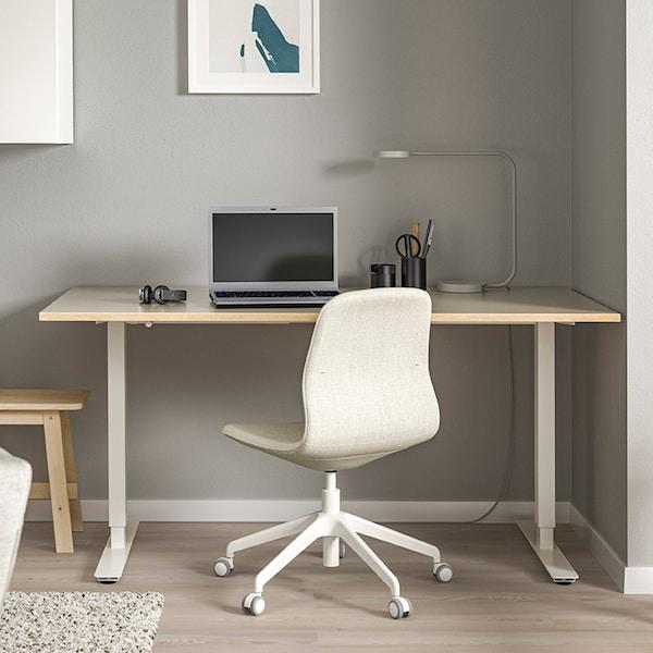 Viihtyisä kotitoimisto, jossa puukantinen pöytä ja valkoinen työtuoli sekä kannettava tietokone.