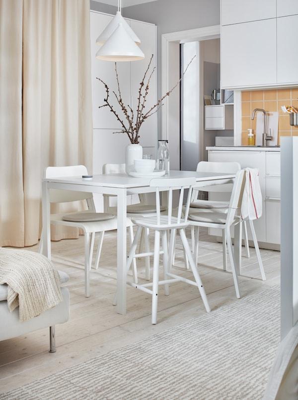 Világos és fehér, egyszobás lakás MELLTORP asztallal és TEODORES székekkel egy apró konyha és egy ágy között.