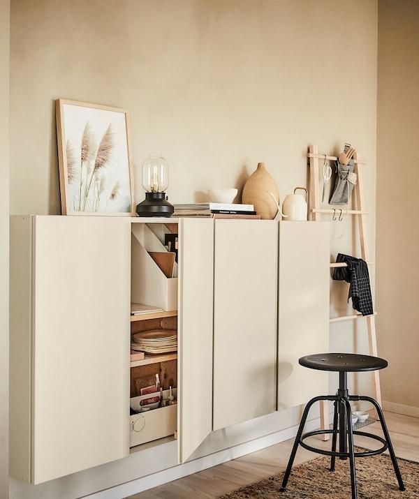Világos fa témájú szoba: fali panel, faliszekrények, szőnyeg és dekorációk; fekete ülőke.