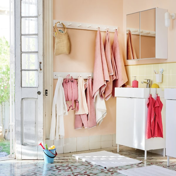 Világos fürdőszoba, különböző törölközőkkel, rózsaszín és korall színben, falon lógó táskákkal.