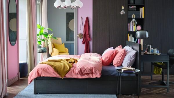 Világos hálószoba egy feketés-barna MALM ággyal, színes ágyneműk, és egy nagy PAX/FORSAND gardrób az egyik falnál.