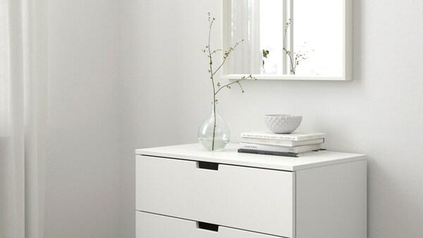 Világos, skandináv stílusú hálószoba, fehér IKEA NORDLI fiókos szekrénnyel, könyvekkel és vázával.