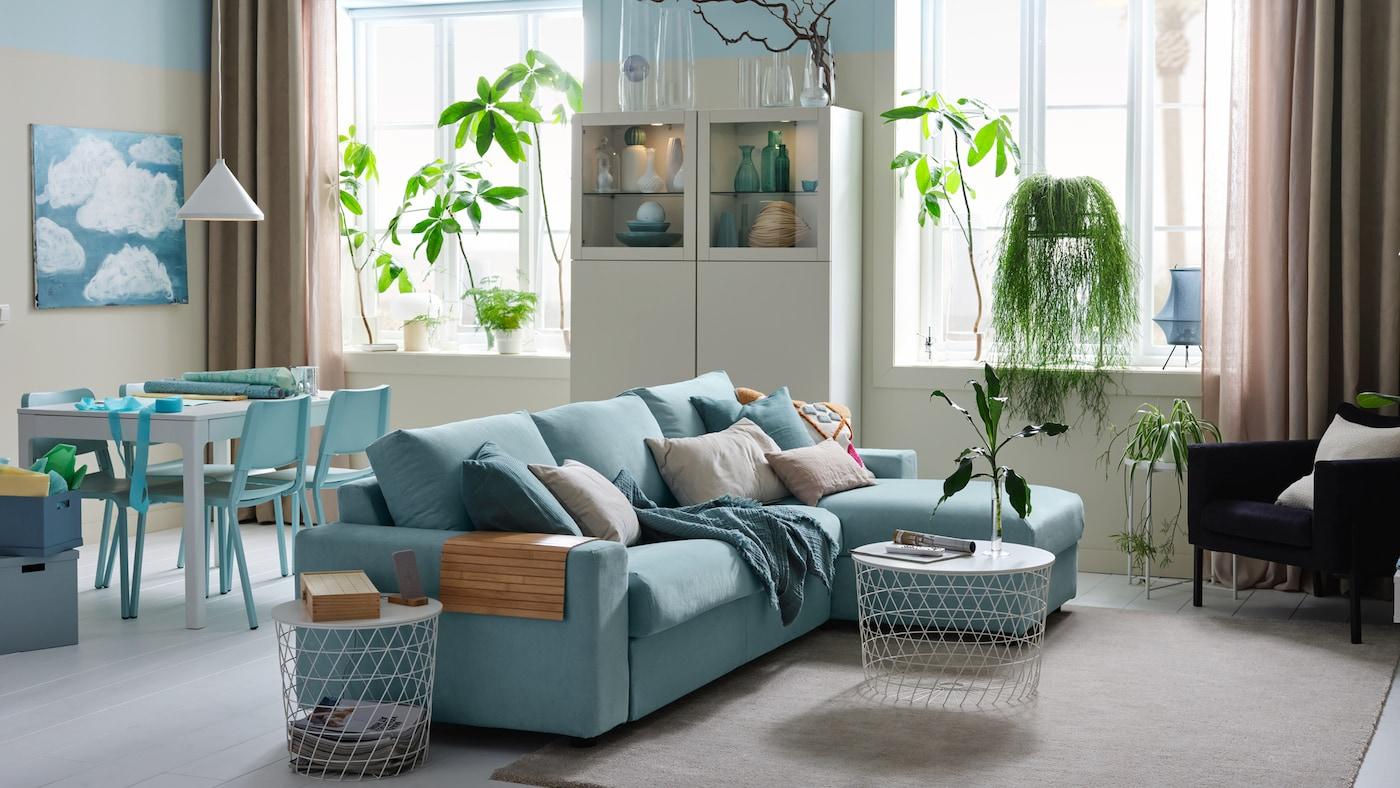 Világos stúdió 3-üléses kanapéval, fekvőfotellel, fehér tárolókombinációval és étkezővel.