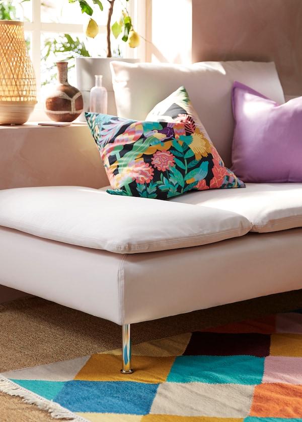 Világos színvilágú kanapé, színes párnákkal és vidám, tarka szőnyeg.