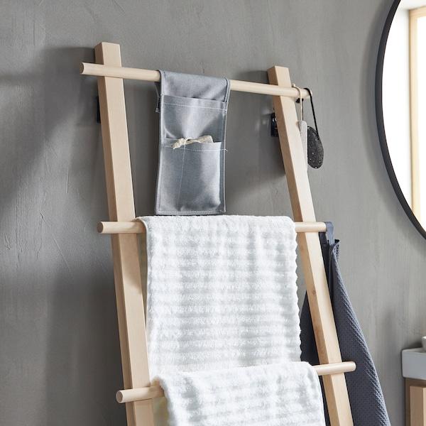 VILTO håndklædestativ af birk, der minder om en stige, står op ad en grå væg på et minimalistisk badeværelse.