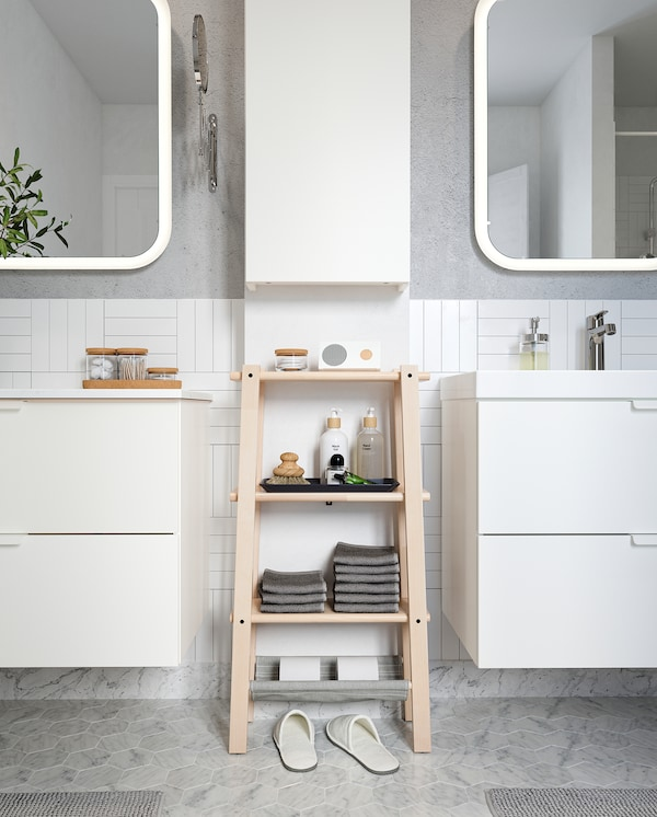 VILTO shelving unit in birch stands between two wash-stands and offers easy-reach storage for folded towels and perfumes.