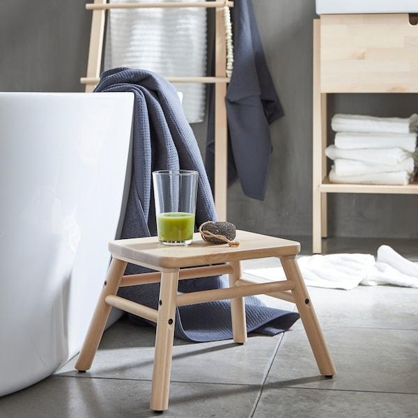 VILTO stoličica od breze, pored kade, s čašom zelenog smutija u minimalističkom kupatilu.