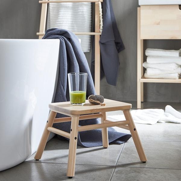 VILTO taburet af birk står ved siden af et badekar med et glas med en grøn smoothie på et minimalistisk badeværelse.