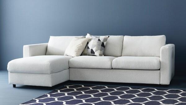 VIMLE 3-zitsbank, met chaise longue in een vrijwel lege donkergrijs, blauwe kamer met zwartwit tapijt en bijzettafel.