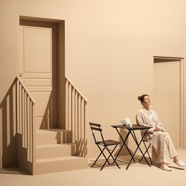 Vinkkejä kuinka sisustaa pienempi ulkotila. Nainen istuu beigesävyisessä kuvassa tuolilla pöydän vieressä.