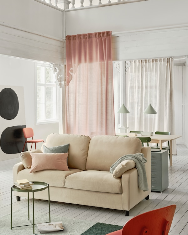 VINLIDEN sofa in beige with generous dimensions standing in a living room with a rug and small table in the foreground.