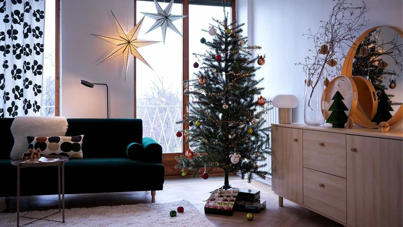 VINTER 2021 Christmas tree is decorated with baubles in a living room beside a green sofa and hanging stars.