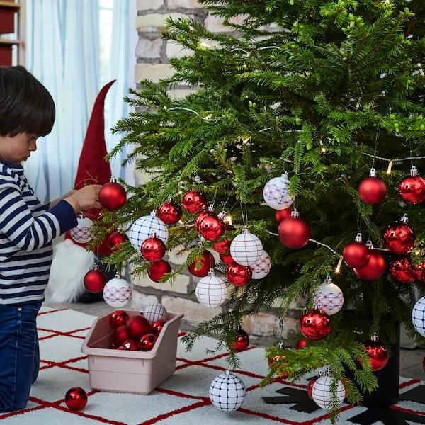 레드와 화이트 패턴이 그려진 VINTERFEST 빈테르페스트 장식공으로 아이가 크리스마스트리를 꾸미고 있는 모습