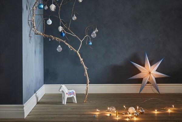 나뭇가지에 VINTERFEST 빈테르페스트 크리스마스 트리 장식이 있으며 근처에는 나무말과 STRÅLA 스트롤라 조명이 놓인 모습