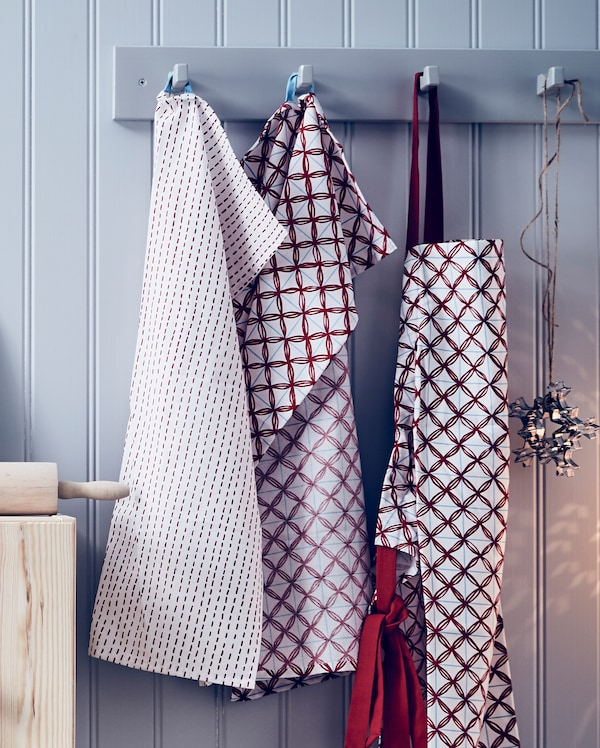 VINTERFEST towels hanging from a wall fitting with a red bag and Christmas decorations.