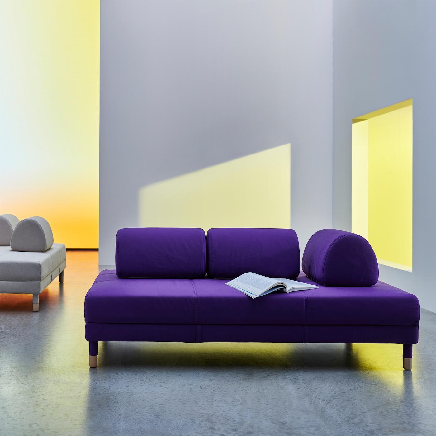 Violetti FLOTTEBO vuodesohva, jossa on minimalistinen muotoilu, puhtaat linjat ja pyöristetyt, siirrettävät tyynyt, jotka voi sijoittaa haluamiinsa kohtiin.