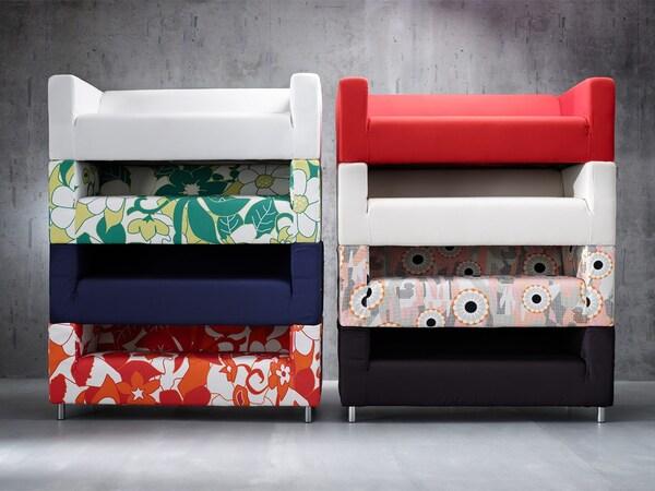 Вісім IKEA KLIPPAN ІКЕА КЛІППАН диванів зі знімними чохлами різного кольору та візерунку, розміщені один на одному.
