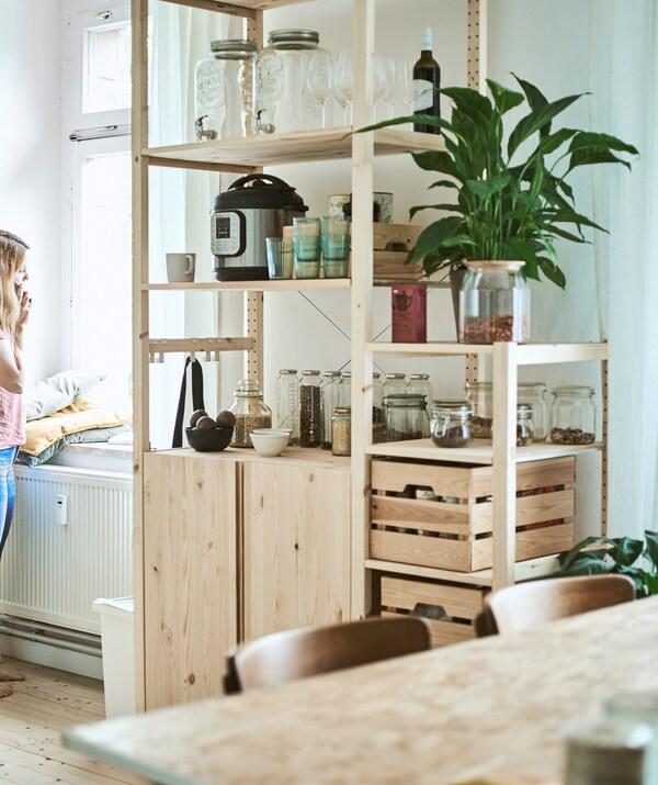 Visoki drveni regal u kuhinji/blagovaonici sa staklenkama, drvenim sanducima i kuhinjskim uređajima na policama.