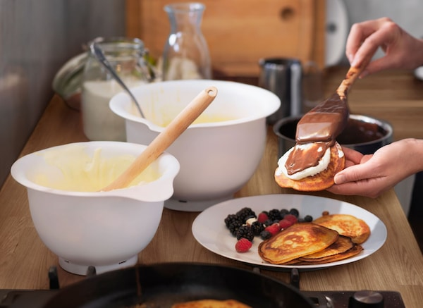 VISPAD mixing bowls in white on top of a worktop with a plate of pancakes, berries and chocolate