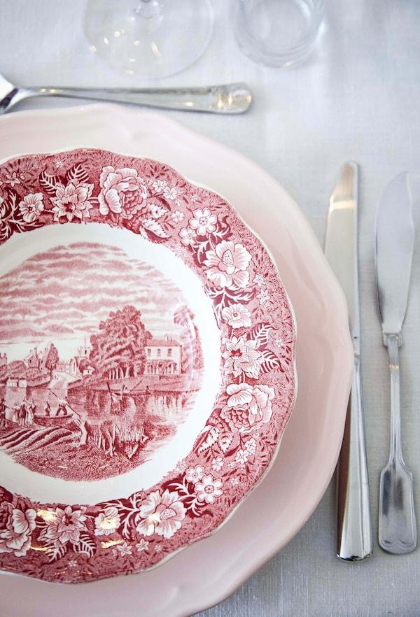 Vista aérea de un plato blanco y rojo y cubiertos de estilo tradicional.