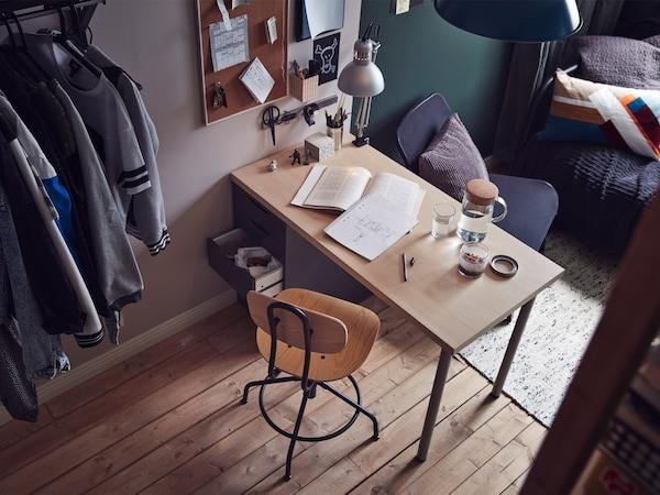 Vista angular del dormitori on es veu un escriptori i una cadira davant i un divan al fons.