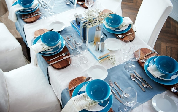 Vista cenital de una mesa de comedor con una presentación formal en blanco y azul.
