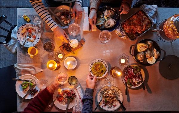 Vista de una mesa de comedor preparada para una comida con un mantel monocromático y una mezcla desenfadada de vajilla, textiles y velas.
