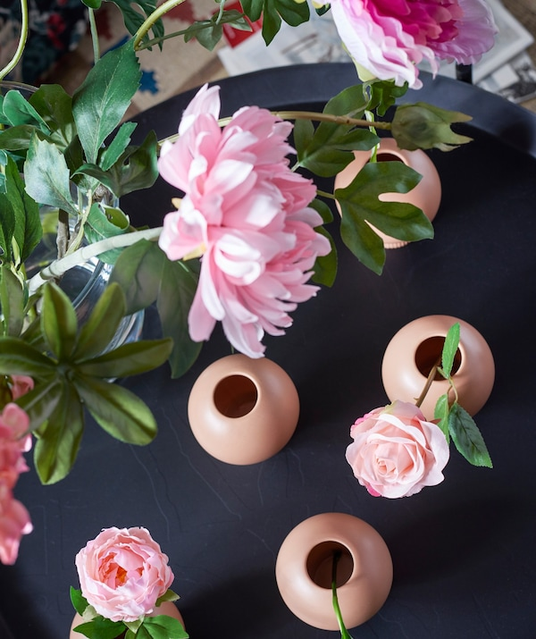 Vista desde arriba de flores rosas artificiales IKEA SMYCKA en pequeños jarrones.