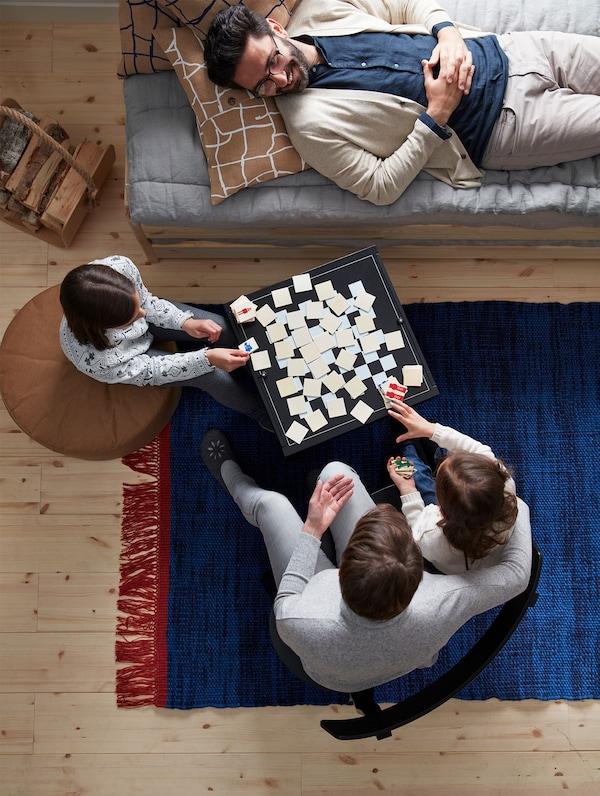 Vista desde arriba, una familia se relaja en el salón jugando en la mesa con tablero de ajedrez VÄRMER.