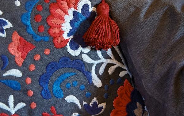 Vista en detalle de la funda de un cojín, bordada con laboriosos estampados de diferentes colores y una borla colgando de una esquina.