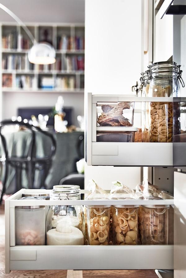 Vista lateral de cajones de la cocina abiertos, llenos de envase de cristal que contienen comida.