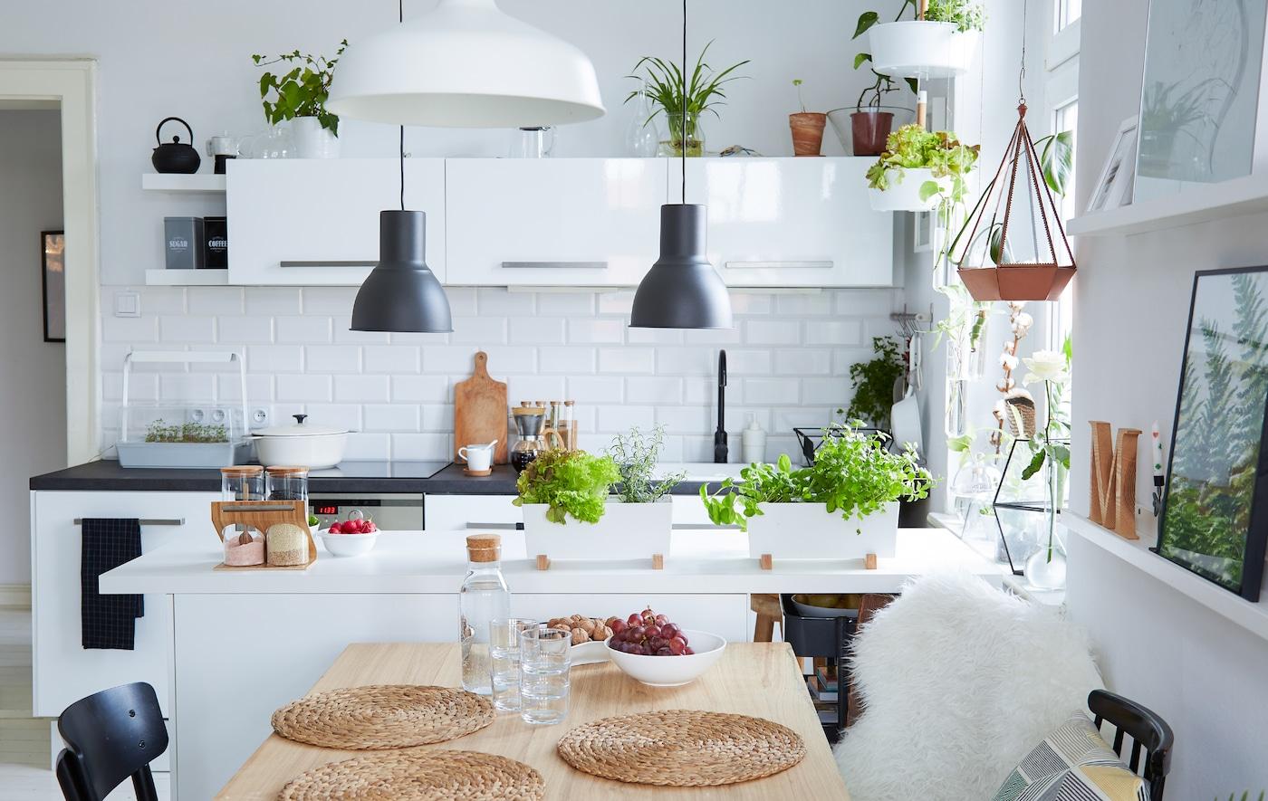 Vista lateral d'un menjador i una cuina de planta oberta. Dos llums d'estil industrial que pengen en una illa de cuina.
