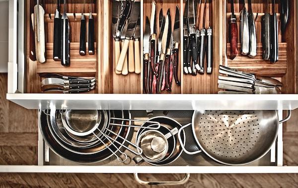 Vista superior de cajones de la cocina abiertos, que muestran ollas y cacerolas y un montón de utensilios en compartimentos del cajón.