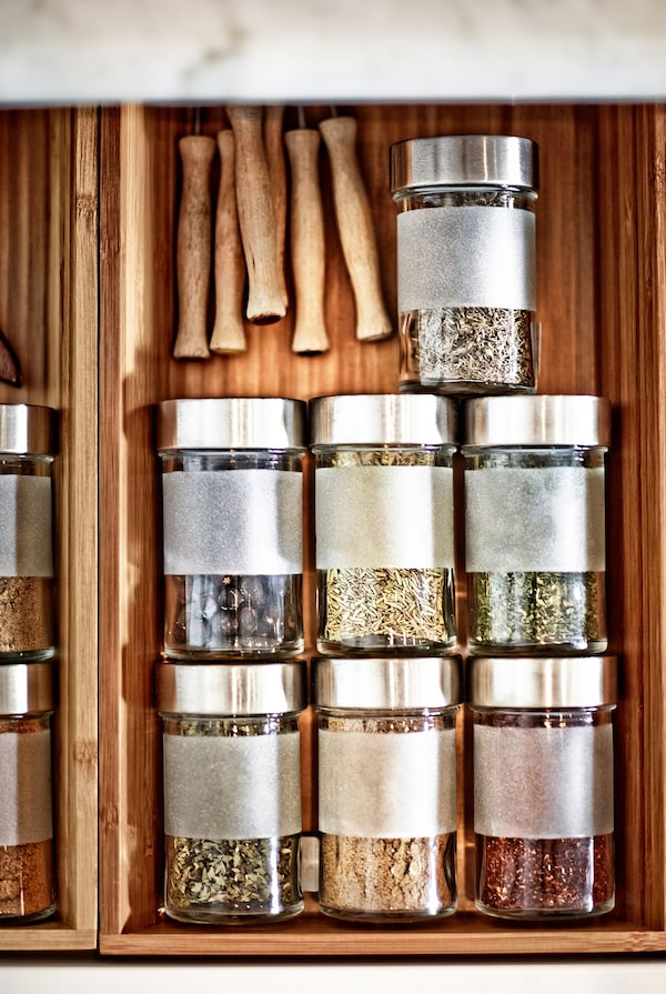 Vista superior de hierbas almacenadas en un estante adicional de un cajón de cocina poco profundo.