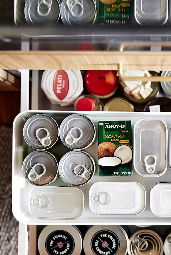 Vista superior de un cajón de cocina abierto con productos secos. Se divide usando los estantes adicionales y envases de almacenaje.