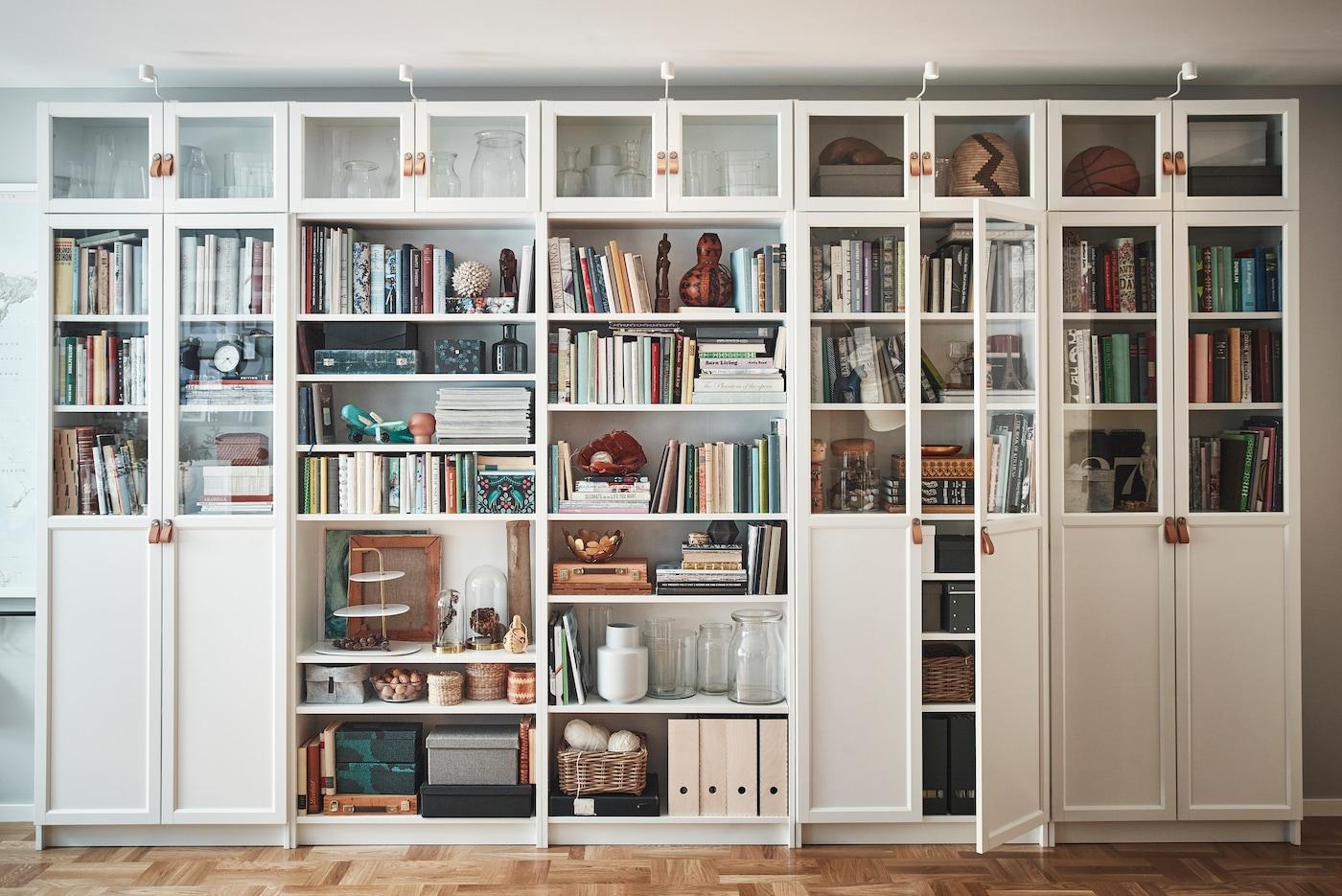 Vit bokhyllekombination BILLY byggd på höjden med vitrindörrar och integrerad belysning.