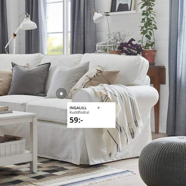 Vit EKTORP soffa med kuddar i naturnära färger,