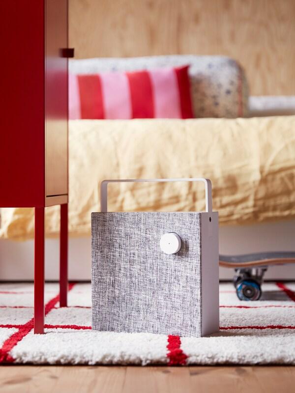 Vit ENEBY Bluetooth-högtalare står på en vit och röd matta i ett modernt, ljust sovrum med träpanel på väggen.