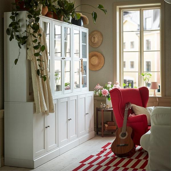 Vit förvaringskombination med glasdörrar i ett vardagsrum i rött och vitt. Ovanpå står några gröna växter.