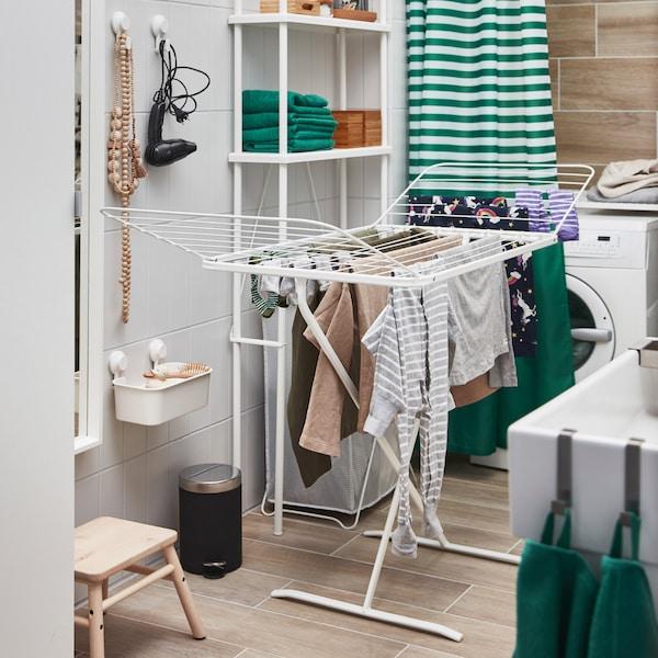 Vit MULIG torkställning med två utfällbara vingar står framför en tvättmaskin där kläder har hängts upp på tork.