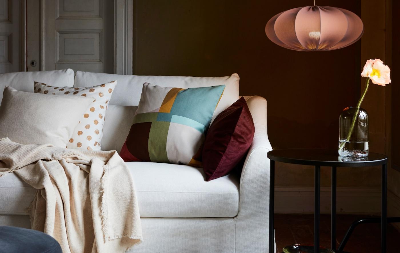 Vit soffa i ett vardagsrum med en mix av kuddar samt en pläd. Intill syns ett svart sidobord och en REGNSKUR lampa.