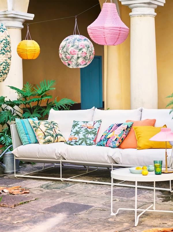 Vit soffa med olikfärgade och mönstrade kuddar står utomhus under flera olika hängande lyktor.