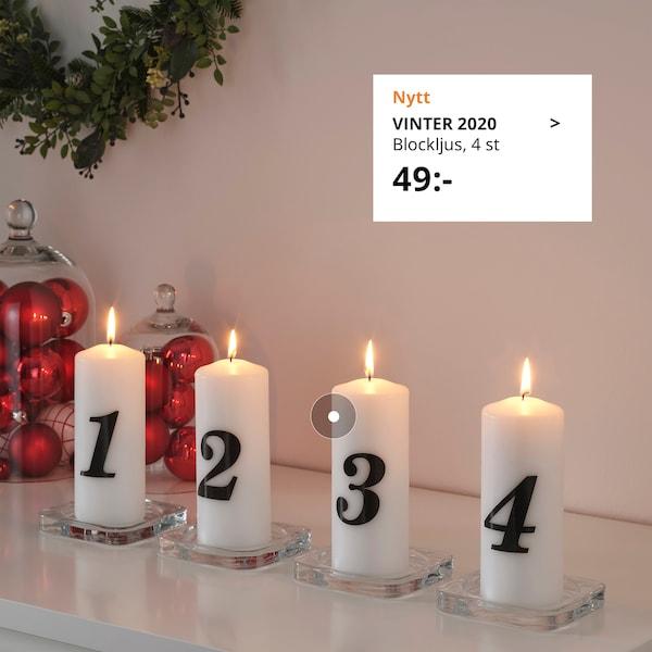 Vita blockljus i adventstema med varsin siffra på står på en blank yta.